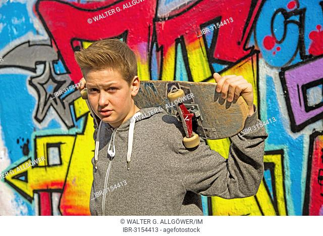 Boy, 13 years, holding a skateboard in front of graffiti-covered wall