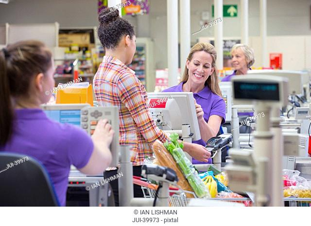 Woman Paying For Shopping At Supermarket Checkout