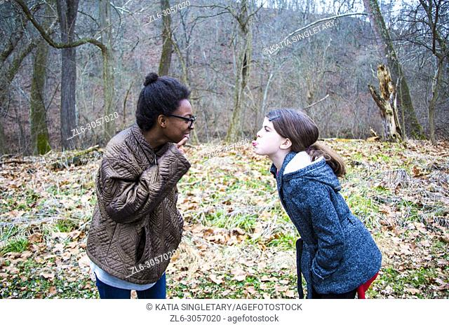 Two teens/ Pre-teens arguing. One African American teen girl, yelling and correcting her caucasian friend/sister. She is bossing her around