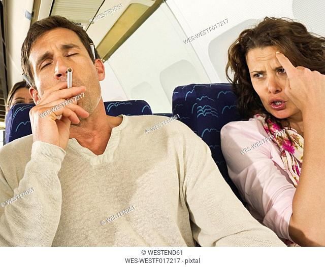 Germany, Munich, Bavaria, Man smoking and women getting annoyed in economy class airliner
