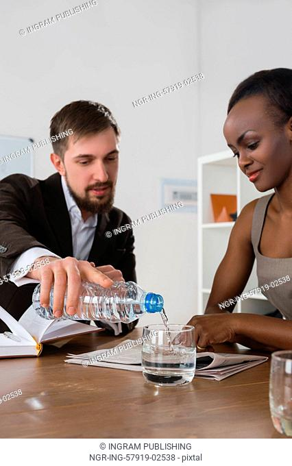 Caucasian businessman pouring water to his african colleague during the business meeting