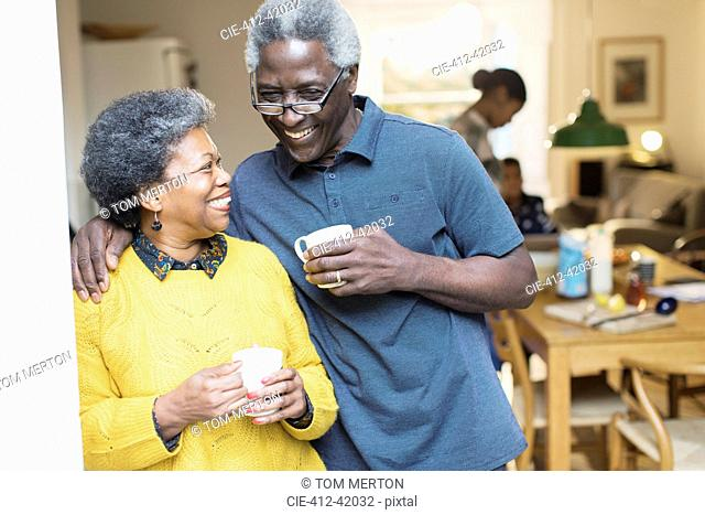 Happy, affectionate senior couple drinking coffee