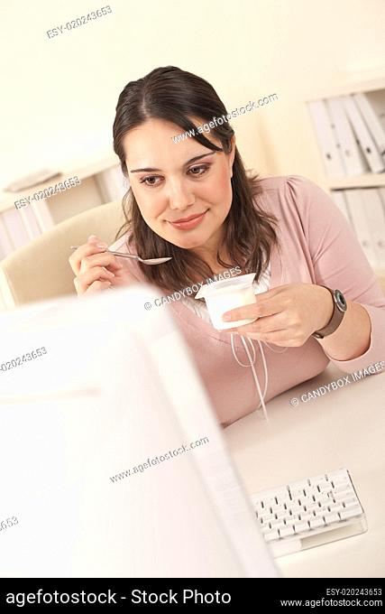 Young businesswoman eating yogurt at office