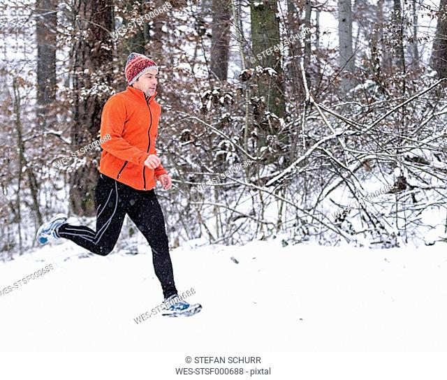 Germany, Baden-Wuerttemberg, Holzberg, man jogging in snow