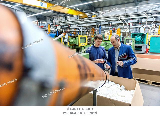 Manager and worker examining plastic products in factory