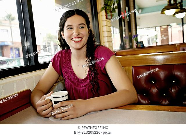 Mixed race woman having coffee in restaurant