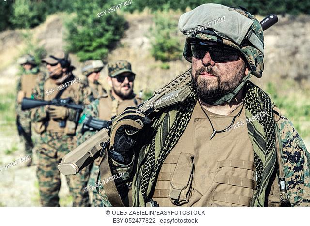 Location shot of United States Marine with rifle weapons in uniforms. Military equipment, army helmet, warpaint, smoked dirty face, tactical gloves