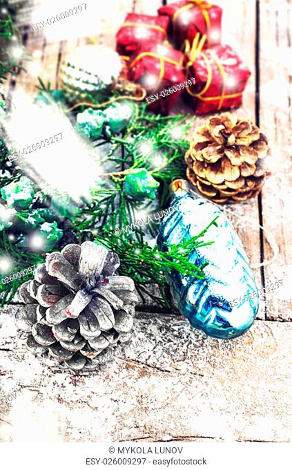 Christmas decorations under the branches of fir tree on snowy wood plank