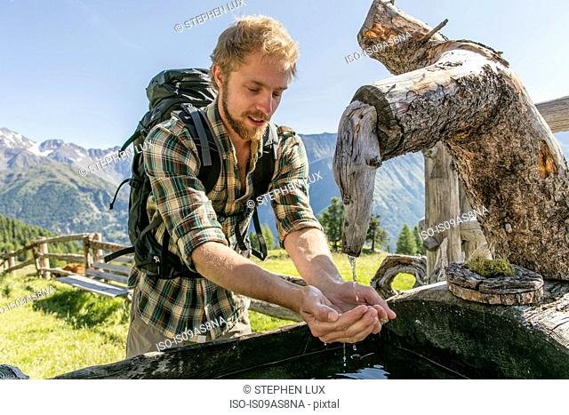 Young male hiker drinking water from rustic trough, Karthaus, Val Senales, South Tyrol, Italy