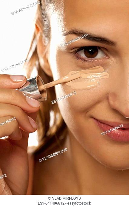young woman applying a liquid foundation on her face