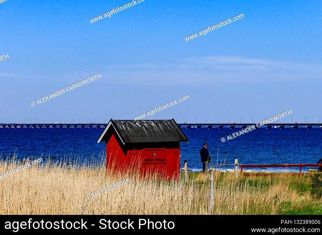 Farjestaden, Oland, Sweden A man stands next to a red cabin overlooking the Oland bridge. | usage worldwide. - /ÖLAND/Sweden