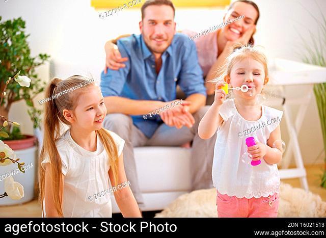 Glückliche Familie zu Hause beim Seifenblasen pusten im Wohnzimmer