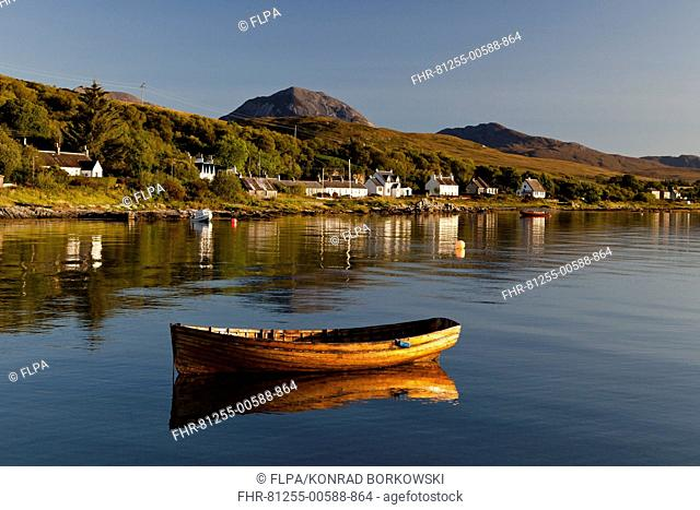 View of small wooden boat and village houses in bay, in morning sunlight, with Beinn Shiantaidh and Corra Bheinn, Paps of Jura in background, Craighouse