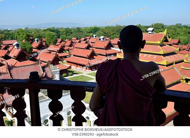 Myanmar, Mandalay, Buddhist monk watching the royal palace from the top of the watchtower
