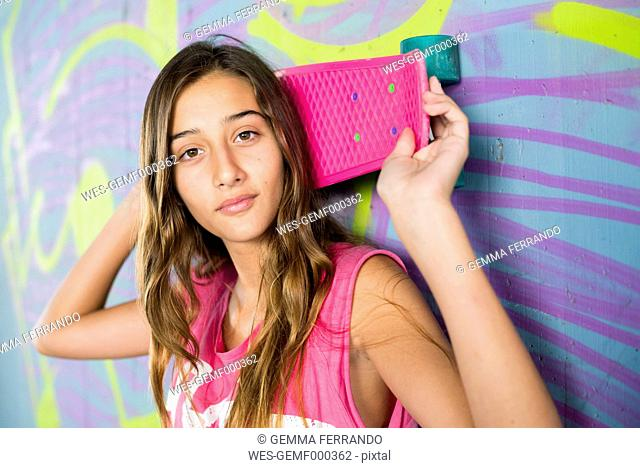Portrait of teenage girl holding a skateboard in front of wall with graffiti