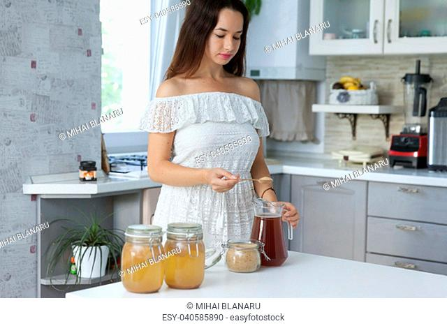Young woman having a break with a glass of fermented green tea into a tea pot