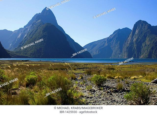 Milford Sound, landmark Mitre Peak and surrounding mountains reflected in the calm waters of Milford Sound, Fiordland National Park, South Island, New Zealand