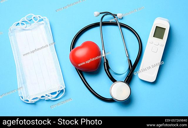 non-contact thermometer, stethoscope and a stack of masks on a blue background, top view