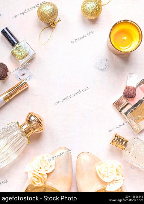 Holiday feminine cosmetic background in golden colour. Cosmetic objects frame with gold heels, christmas balls, gold glitter nail polish, perfume bottle