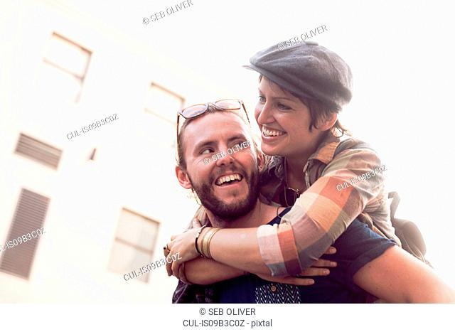 Man giving girlfriend piggyback on street