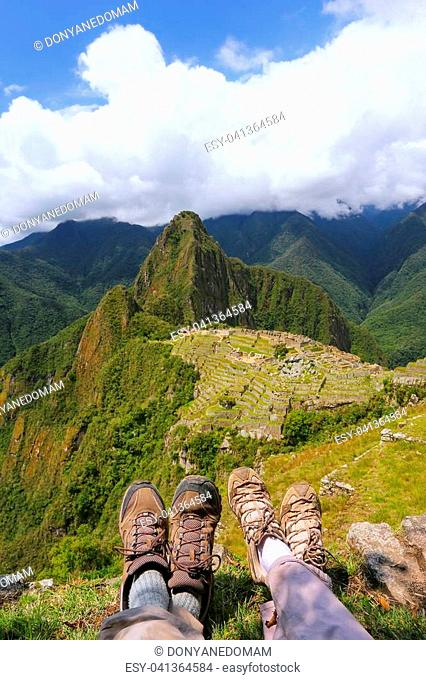 Couple of hikers resting at Machu Picchu overlook in Peru. In 2007 Machu Picchu was voted one of the New Seven Wonders of the World
