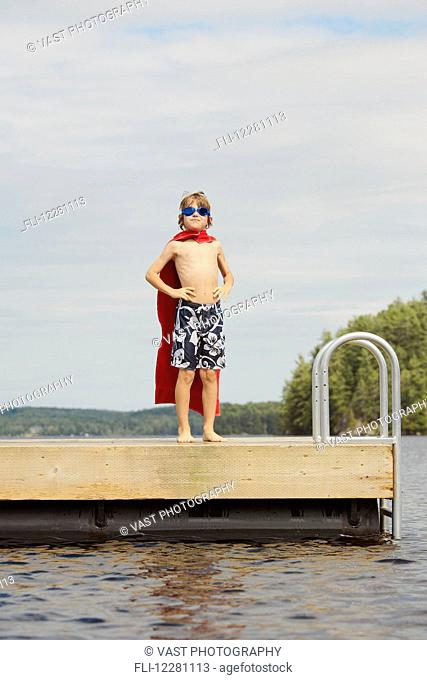 Boy standing on dock wearing goggles and towel pretending to be a super hero; Ontario, Canada