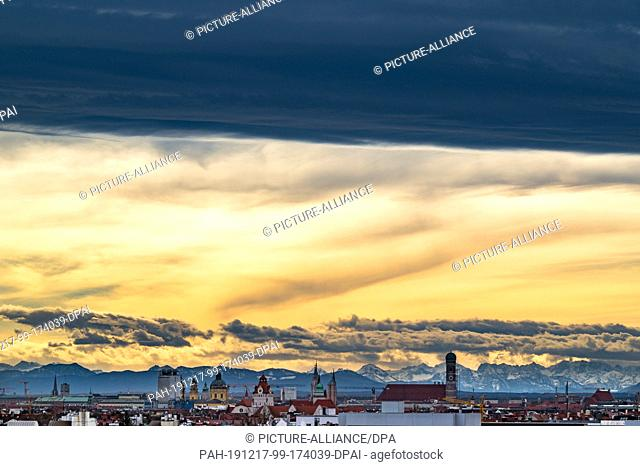 17 December 2019, Bavaria, Munich: A dark band of clouds hangs over the Bavarian capital, whose centre is marked by the high towers of the Frauenkirche (centre...