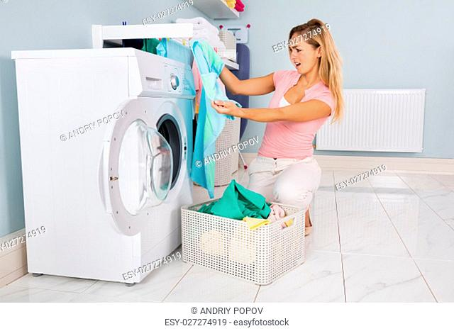 Young Woman Looking At Clothes After Washing In Washing Machine At Utility Room