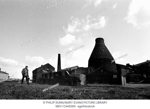 A man walks past a redundant pottery with its chimney and bottle oven in The Potteries, Stoke-on-Trent, Staffordshire, England