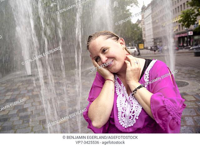 Woman under fountain water spray, Munich, Germany