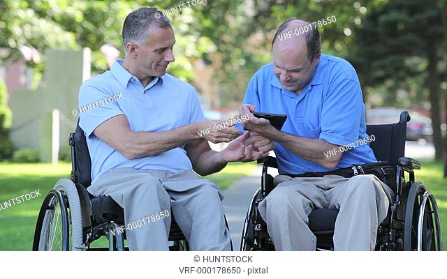 Two men in wheelchairs in a park reading a digital tablet one with spinal cord injury and one with Friedreich's Ataxia