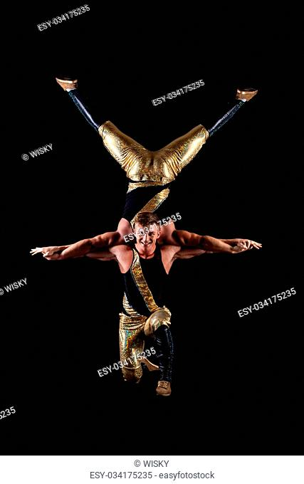 Smiling muscular acrobats isolated on black background