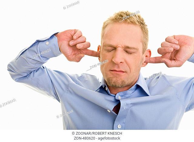Blonder Mann hat die Augen geschlossen und hält sich die Ohren zu