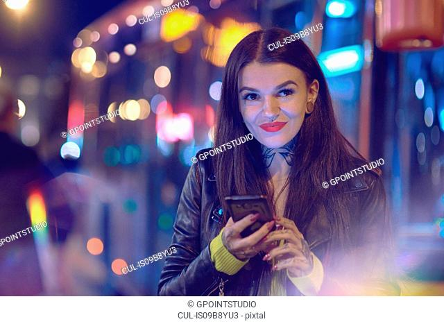 Young woman outdoors at night, holding smartphone, tattoos on hand and neck