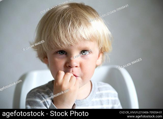 Caucasian boy eating in the kitchen, lifestyle portrait