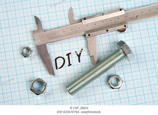 Do it yourself - Screw, Nuts and caliper on graph paper background
