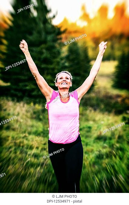 A vintage looking shot of an attractive middle-aged woman wearing active wear running with her hands in the air in a city park at sunset during a warm autumn...