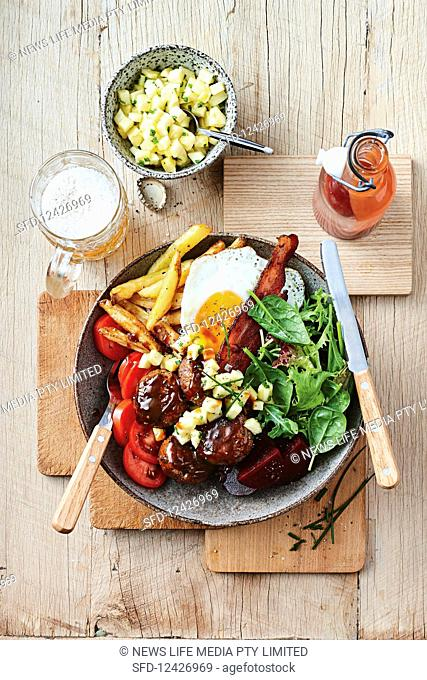 An Aussie burger with a fried egg, fries and vegetables
