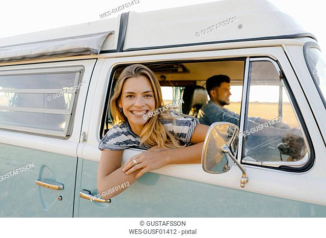 Portrait of happy woman leaning out of window of a camper van with man driving