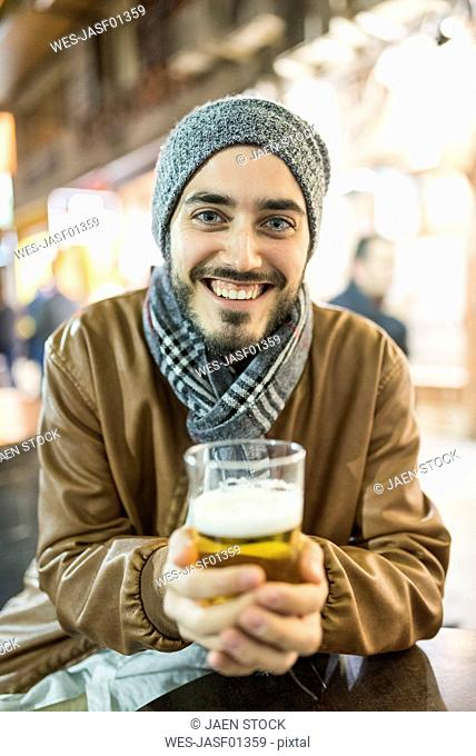 Smiling man with beer at outdoor bar