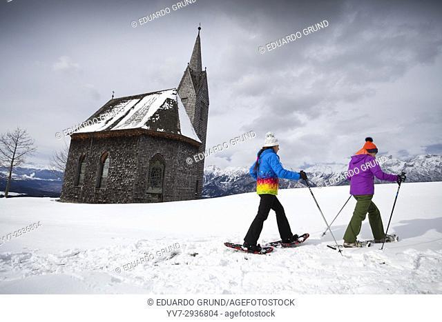 Chicas excursionistas con raquetas de nieve en las inmediaciones de la iglesia de madera de Windegg