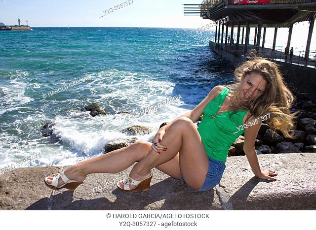 Beautiful, attractive Ukrainian woman wearing a green shirt and shorts posing near the black sea for a photographic sequence in Yalta, Crimea
