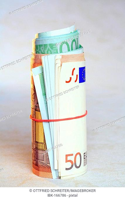 Rolled Euro bank notes with a rubber ring