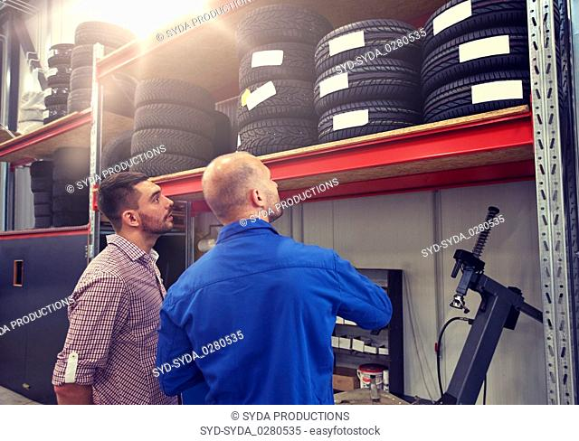 mechanic and man choosing tires at car shop