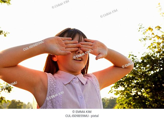 Girl covering eyes for hide and seek in park