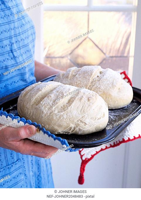 Woman holding bread on baking tray