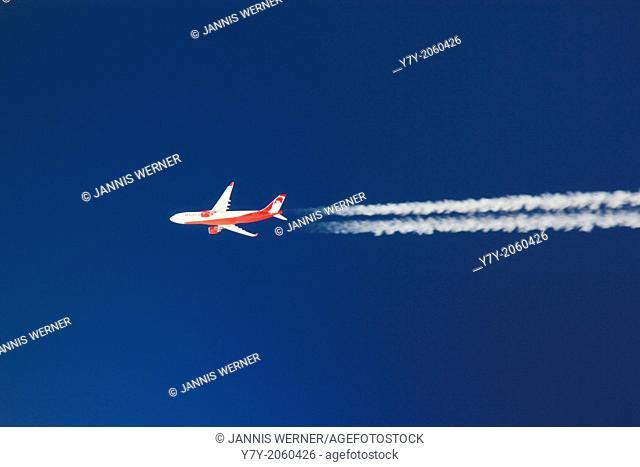 Air Berlin airplane brightly lit in a clear deep blue sky