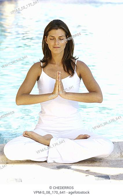 Young woman meditating by the poolside