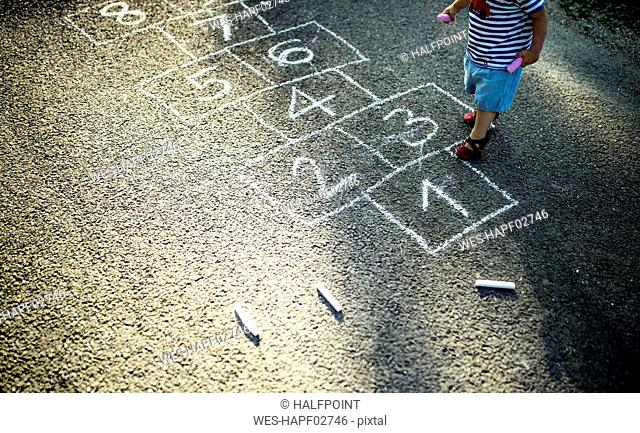 Little girl with drawn hopscotch on the street, partial view