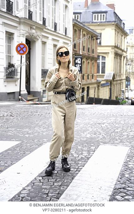 fashionable woman standing at street during fashion week, in Paris, France